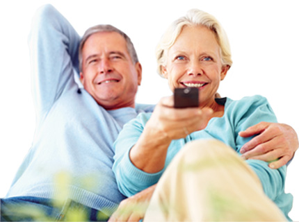 A picture of an elderly couple with a remote control